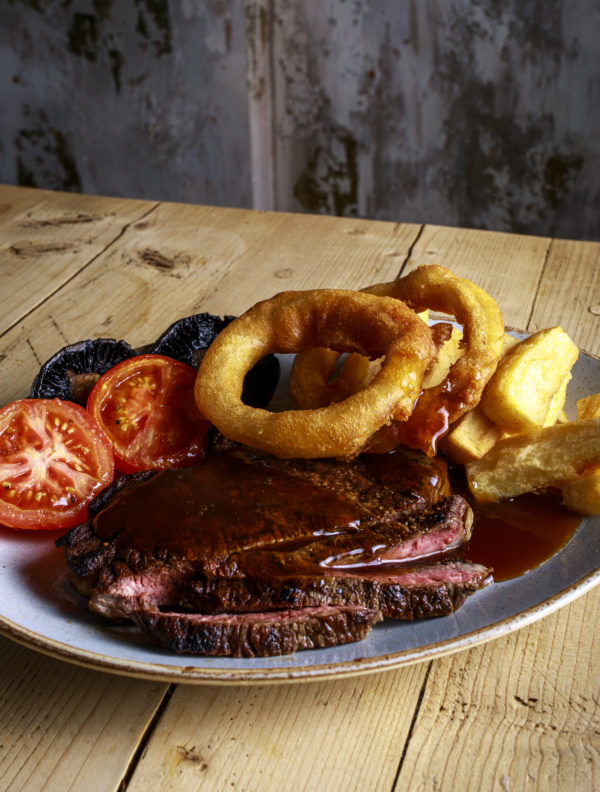 Steak on a plate with tomatoes, mushrooms and onion rings